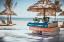 Stack of books and sunglasses in beach setting